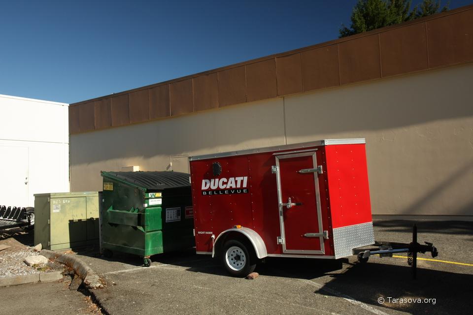 Красный фургончик и простой мусорный бак