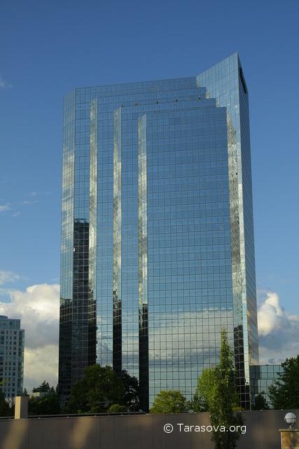 Многоэтажное здание с его зеркальным стенами сливается с небом
